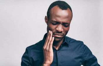 Man Grasping His Jaw with Tooth Pain